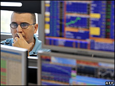 A broker looks at a stock exchange screen in Budapest