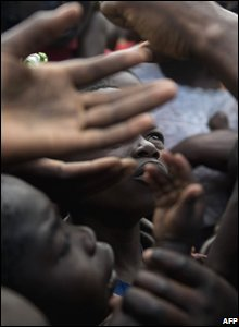 Children reach for food vouchers at a camp in Kibati. near Goma