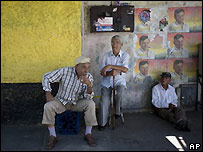 Hombres sentados en Caracas frente a un muro cubierto de afiches de propaganda política