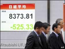 Pedestrians walk past board showing market prices in Tokyo, Japan (07/11/2008)