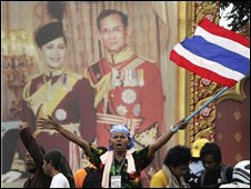 Anti-government demonstrators wave the national flag in front of a portrait of King Bhumibol Adulyadej and Queen Sirikit in Bangkok on 29 August 2008
