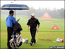 Graeme McDowell braves the rain at the practice ground