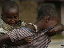 A young girl and her sibling look for their parents in Protegee, carrying her sibling on her back, cries as she looks for her parents through the village of Kiwanja, DR Congo, on 6 November 2008