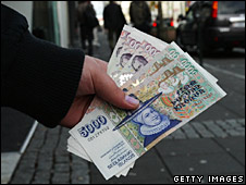 A bank customer holds a handful of Icelandic crowns