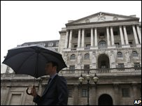 A man with an umbrella walks past the Bank of England