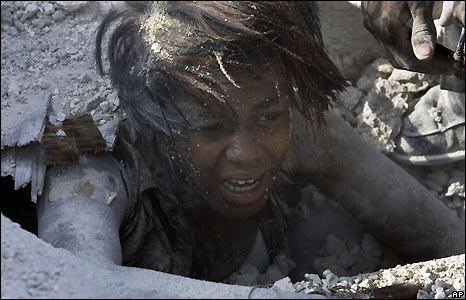 A woman climbs out of rubble of collapsed school