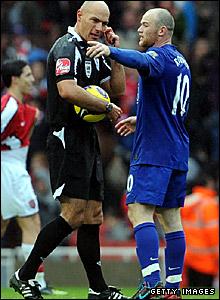 Referee Howard Webb talks to Manchester United's Wayne Rooney at half-time