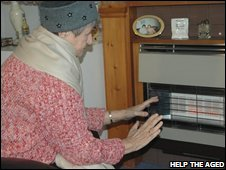 Elderly woman in front of heater