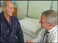 Dr Stephen Allen yn trafod yr arbrawf gyda chlaf, Giuseppe Guadagnino