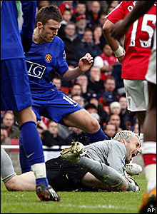 Manchester united's Michael Carrick challenges Arsenal keeper Manuel Almunia