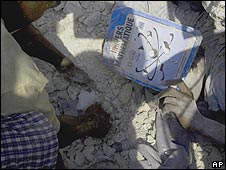 Hands digging through the rubble find a maths text book