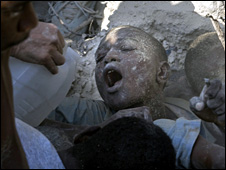 A boy trapped in the rubble is given water before being pulled out by rescuers (7 November 2008)