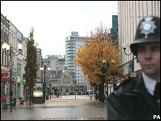 Police officer guarding closed-off area of Ilford town centre