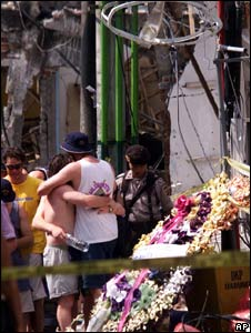 Australian tourists hug at the site of the 2002 bomb blast