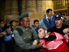 Israeli policemen scuffle with an Armenian altar boy during a fight at the Church of the Holy Sepulchre on 9 November2008