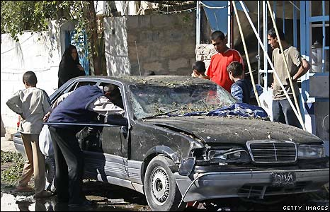 A man examines a car after the triple bombing - 10/11/2008