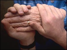 Elderly patient being helped by a carer