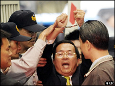 Chen Shui-bian (centre) raises his handcuffed-hands outside the prosecutor's office in Taipei