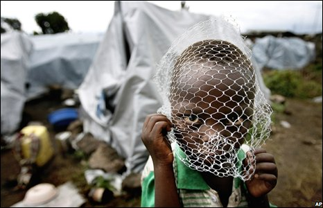 "A 3-year-old boy covers his face with a net ""against mosquitoes"" at the Kituku displaced camp in Goma"