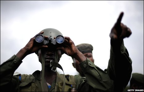 A Congolese army soldier looks through binoculars at a check point on a road leading to Goma