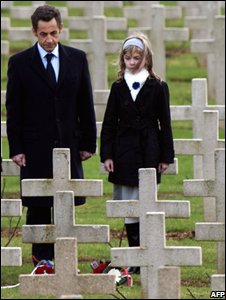 France's President Nicolas Sarkozy and an unidentified schoolgirl pay their respect in the WWI cemetery near Verdun