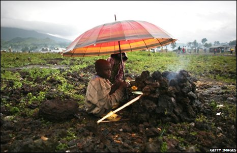 Congolese children shelter under an umbrella at the Kibati refugee camp just outside the town of Goma, Congo