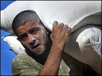 عامل فلسطيني يحمل جوال دقيق