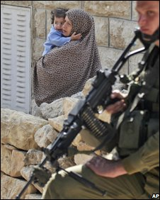 A Palestinian woman and child walk behind an Israeli soldier in Hebron