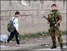 An Italian paratrooper patrols a street near Caserta, southern Italy (October 2008)