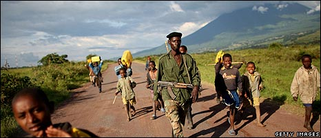 Generic image of Congolese rebel soldier walking with children