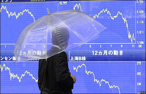 A pedestrian walks past a share prices chart in Tokyo