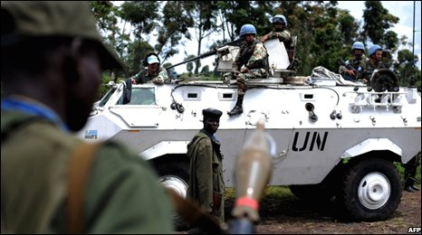 Congolese army soldiers stand next to a UN Peacekeepers vehicle on the outskirts of Goma