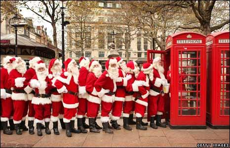Santa performers queue at a phone box
