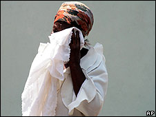 Zimbabwean woman weeps at funeral for her niece and unborn child, victims of a cholera outbreak