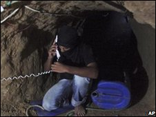 A smuggler uses a phone inside the tunnel