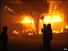 Firefighters by a burning home in Montecito, California