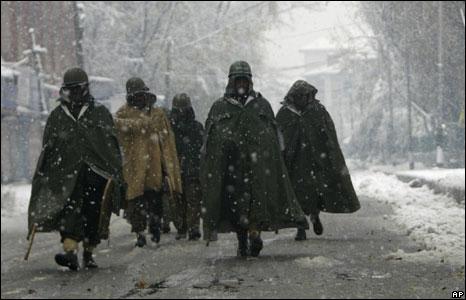 Indian soldiers patrol a deserted street in snowy Srinagar in Indian Kashmir