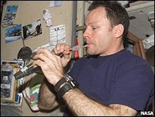 An astronaut drinks on board the space station