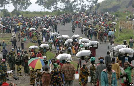 People leave the aid distribution point at a camp in Kibati, north of Goma