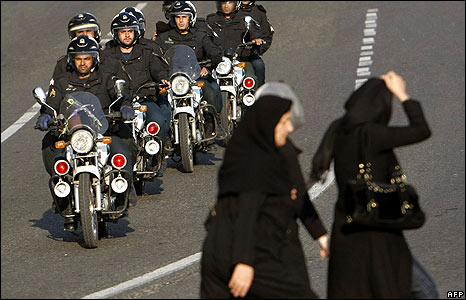 Iranian women pass a police motorcycle unit in Tehran