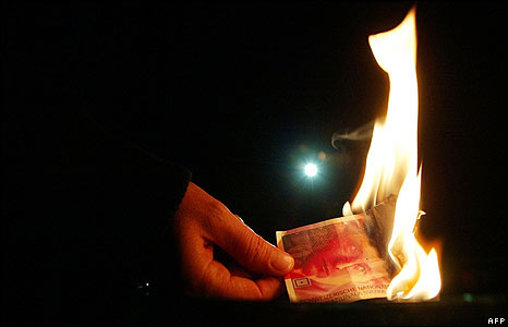 A person burns a real Swiss banknote at an anti-capitalism event in Zurich
