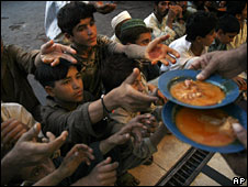 People reach for donated food rations in Karachi, 8 Nov