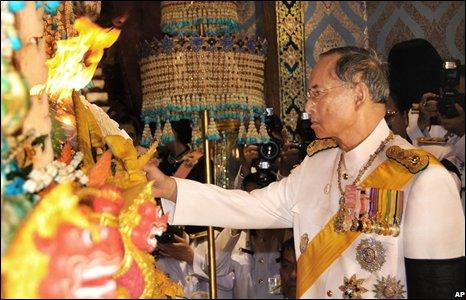Thai King Bhumibol Adulayadej  lights the pyre (Image from Thai Royal Bureau)