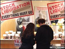 "A couple look at the jewelery for sale in a shop adorned with posters advertising "" Stock Liquidation "" on London's Bond Street"