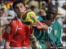 Al Ahly's Ahmad Hassan fights for the ball with Kimgue Mondo of Coton Sport