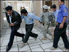 Iraqi policemen dance with a US soldier at a Baghdad police station on 16 November