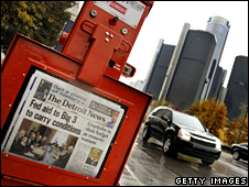 A newspaper box stands near the General Motors world headquarters in Detroit (7 November 2008)