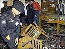 Security personnel inspect the wreckage at a bomb blast site in 2006