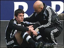 Joey Barton (left) is attended to by Newcastle's physio