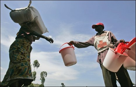 A displaced woman receives a bucket and plastic sheets from the Red Cross in Kibati, eastern Congo